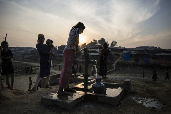 Niña rohingya sacando agua de un pozo.